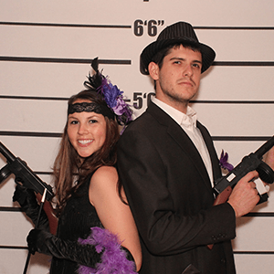 Minneapolis Murder Mystery party guests pose for mugshots